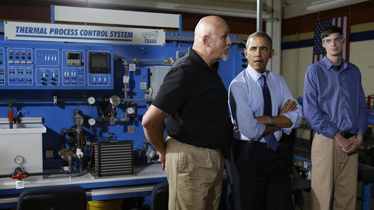 President Barack Obama tours a classroom with Paul Blackford, left, an instructor of the Mechatronics Program, at Community College of Allegheny County West Hills Center, Wednesday, April 16, 2014, in Oakdale, Pa., before speaking about the importance of jobs-driven skills training. (AP Photo/Carolyn Kaster)