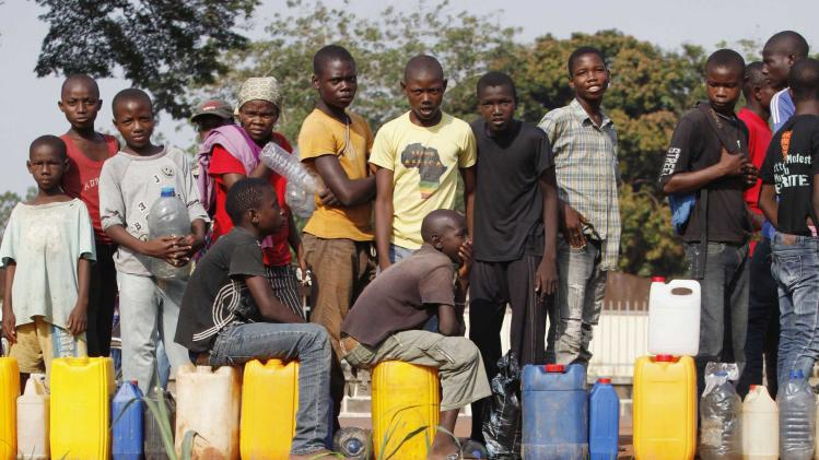Men line up for petrol as they are reflected in the water in Bangui