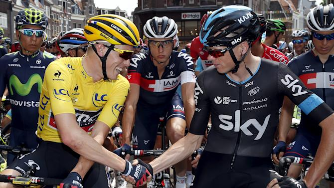 BMC Racing rider Dennis of Australia, leader yellow jersey holder shakes hand withTeam Sky rider  Froome of Britain Utrecht before the start of the 166-km (103.15 miles) second stage of the 102nd Tour de France cycling race