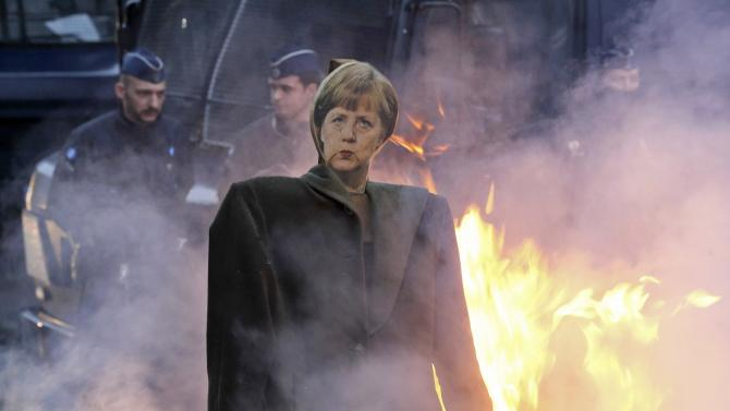 An effigy of German Chancellor Merkel is seen near burning bales of straw set on fire by European farmers during a protest against the TTIP in Brussels