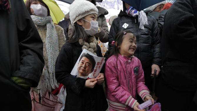 Children chuckle during a speech by Japan's main opposition Liberal Democratic Party (LDP) President Shinzo Abe during a campaign rally for the Dec. 16 parliamentary elections in Kawaguchi, near Tokyo, Saturday, Dec. 15, 2012. Candidates made final impassioned appeals Saturday to voters a day before Japanese parliamentary elections that are likely to hand power back to a conservative party that ruled the country for most of the post-war era. (AP Photo/Itsuo Inouye)