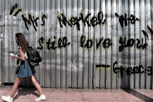 "A young woman walks past a graffiti reading ""Mrs…"