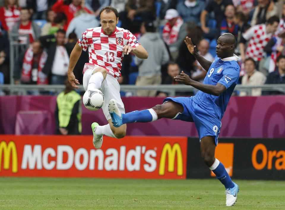 Croatia's Gordon Schildenfeld, left, and Italy's Mario Balotelli fight for the ball during the Euro 2012 soccer championship Group C match between Italy and Croatia in Poznan, Poland, Thursday, June 14, 2012. (AP Photo/Gregorio Borgia)