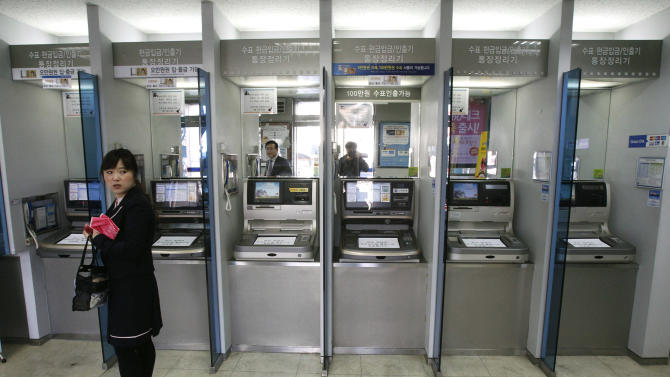 A customer stands in front of automated teller machines at a branch of Shinhan Bank after the bank's computer networks was paralyzed in Seoul, South Korea, Wednesday, March 20, 2013. Police and South Korean officials were investigating the simultaneous shutdown Wednesday of computer networks at several major broadcasters and banks. While the cause wasn't immediately clear, speculation centered on a possible North Korean cyberattack. (AP Photo/Ahn Young-joon)
