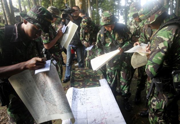 Indonesian soldiers read maps at Taman Nasional Halimun Salak in Sukabumi, West Java, Indonesia, Thursday morning, May 10, 2012. Search and rescue teams were scouring the slopes of a dormant volcano i
