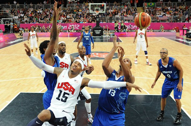 U.S. forward Carmelo Anthony, second from left, reacts after shooting while being challenged by French forward Boris Diaw, right, next to French guard Tony Parker, right, during the men&#39;s basketball preliminary round group A match between the United States and France at the 2012 Summer Olympics, on Sunday, July 29, 2012 in London. (AP Photo/Mark Ralston, Pool)