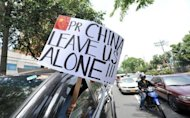 A motorist displays an anti-China placard in front of the Chinese consulate in Manila. Hundreds of Filipinos demonstrated outside the Chinese embassy in the Philippines over an escalating territorial row, with the protesters denouncing China&#39;s rulers as arrogant bullies