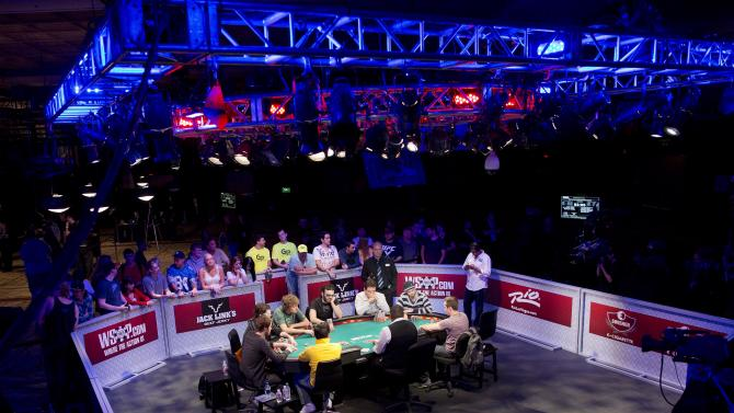 Nine of 25 remaining players engage in a round of Texas Hold 'em during the World Series of Poker, Monday, July 15, 2013, in Las Vegas. More than a dozen eliminations stand between the remaining players in the world series main event and a ticket for a November finale worth $8.4 million to the winner. (AP Photo/Julie Jacobson)