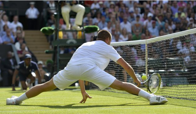 Mikhail Youzhny of Russia hits a shot into the net during his men's singles tennis match against Andy Murray of Britain at the Wimbledon Tennis Championships, in London