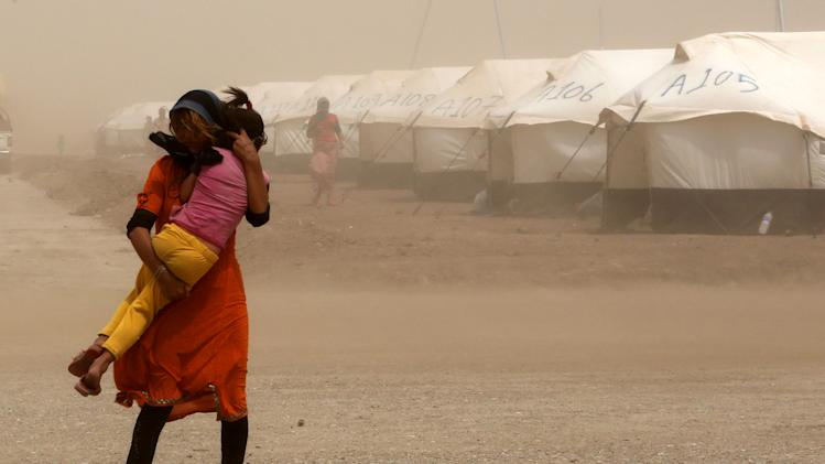 An internally displaced Iraqi woman holds her sister during a sandstorm at a new camp outside the Bajid Kandala camp in Feeshkhabour town, Iraq, Tuesday, Aug. 19, 2014. Some 1.5 million people have been displaced by fighting in Iraq since the Islamic State's rapid advance began in June, and thousands more have died. The scale of the humanitarian crisis prompted the U.N. to declare its highest level of emergency last week. (AP Photo/ Khalid Mohammed)
