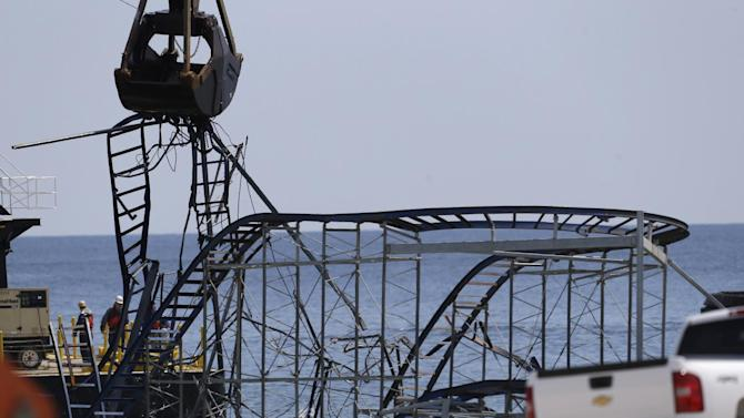 The claw of a crane, left, tears through the structure of the Jet Star Roller Coaster, Tuesday, May 14, 2013, in Seaside Heights, N.J. Workers began to demolish the roller coaster, which fell in the ocean when part of the Casino Pier was washed away by Superstorm Sandy in October. (AP Photo/Julio Cortez)
