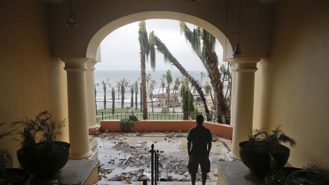 A tourists looks to the ocean from inside a debris-filled area at the Hilton hotel after the resort sustained severe damage from Hurricane Odile in Los Cabos, Mexico,  Monday, Sept. 15, 2014.  Hurricane Odile blazed a trail of destruction through Mexico's Baja California Peninsula that leveled everything from ramshackle homes to big box stores and luxury hotels, leaving roads and entire neighborhoods as disaster zones. (AP Photo/Victor R. Caivano)