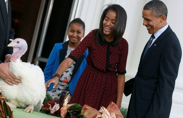 U.S. President Barack Obama is flanked by his daughters Sasha (L) and Malia (R) after pardoning 'Liberty', a 19-week old, 45-pound turkey at the North Portico of the White House November 23, 2011 in W