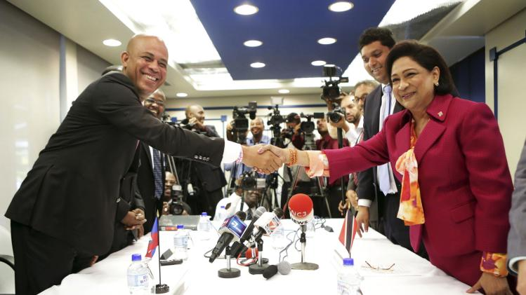 Haiti's President Martelly shakes hands with PM of Trinidad and Tobago Persad-Bissessar after the signing of a memorandum, in Port-of-Spain