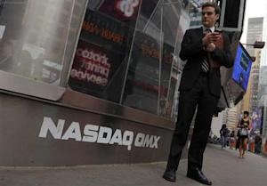 A man stands next to the Nasdaq MarketSite in New York