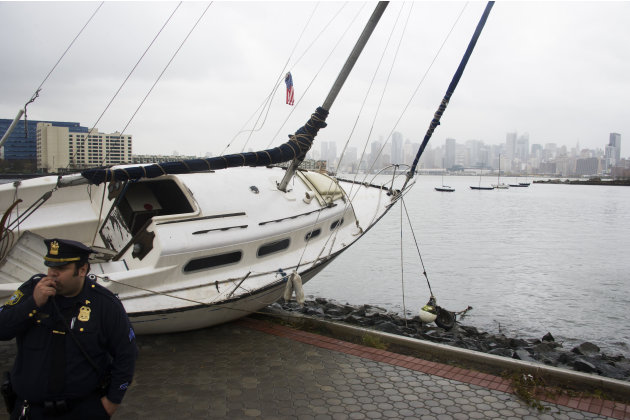 A boat rests on the waterfront of the Hudson River in Hoboken, N.J. across from New York City, background right, on Tuesday, Oct. 30, 2012 after superstorm Sandy made landfall in New Jersey Monday eve