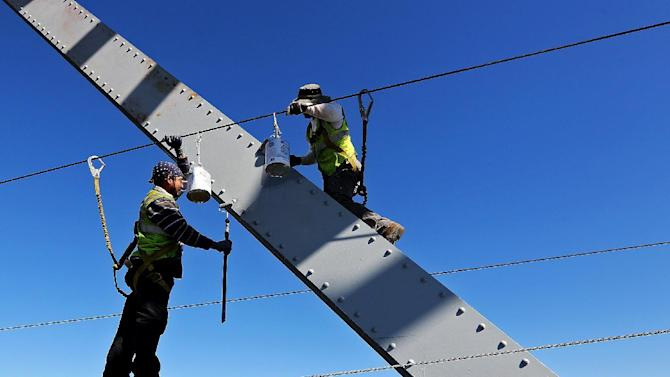 In this Aug. 24, 2015 photo, workers paint the Julien Dubuque Bridge along U.S. 20 in Dubuque, Iowa. The U.S. government issues the August jobs report on Friday, Sept. 4, 2015. (Dave Kettering/Telegraph Herald via AP) MANDATORY CREDIT