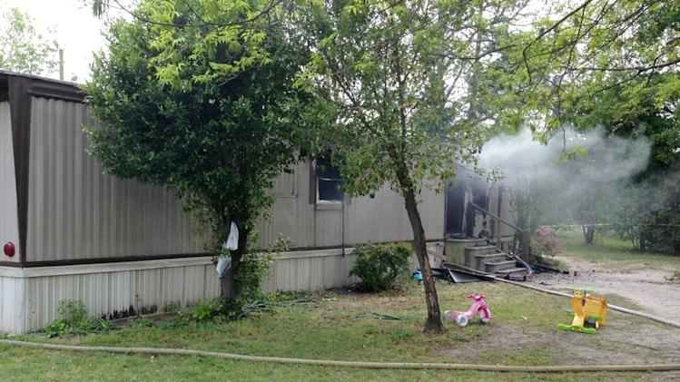 In this photo provided by the Darlington County Sheriff's office, a mobile home in Florence, S.C. smolders after a fire Wednesday, April 24, 2013.  Four children died in the fire, their bodies discovered by firefighters shortly after they put out the flames, an official said. (AP Photo/Darlington County Sheriff via The Morning News)