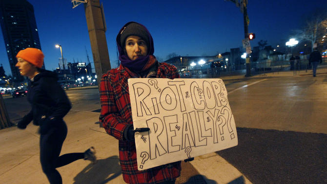 Iris Kirsch displays a sign to passing traffic across the street from the Occupy Baltimore site in response to the protestors' eviction from McKeldin Square in Baltimore, Tuesday, Dec. 13, 2011. Kirsch drove to the site to show support after hearing about the early-morning eviction. (AP Photo/Patrick Semansky)
