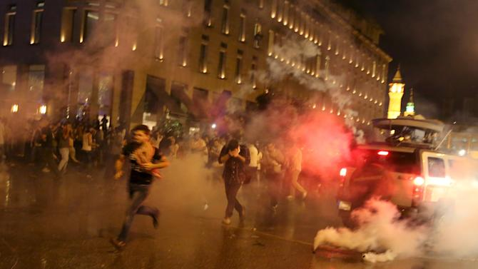 Protesters run from tear gas fired by security forces in Martyr square, downtown Beirut