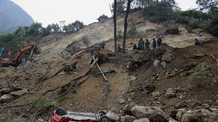 Chinese rescue workers survey a road destroyed by an earthquake in Baoxing county in southwestern China's Sichuan province, Monday, April 22, 2013. The efforts under way Monday in mountainous Sichuan province after a quake Saturday that killed at least 188 people showed that the government has continued to hone its disaster reaction — long considered a crucial leadership test in China — since a much more devastating earthquake in 2008, also in Sichuan, and another one in 2010 in the western region of Yushu. (AP Photo)