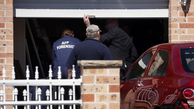 Members of the Australian Federal Police forensic unit enter a garage with equipment at a house that was involved in pre-dawn raids in the western Sydney suburb of Guilford