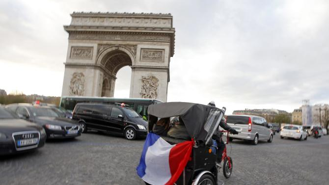 A French national flag hangs from a tricycle near the Arc de Triomphe in Paris
