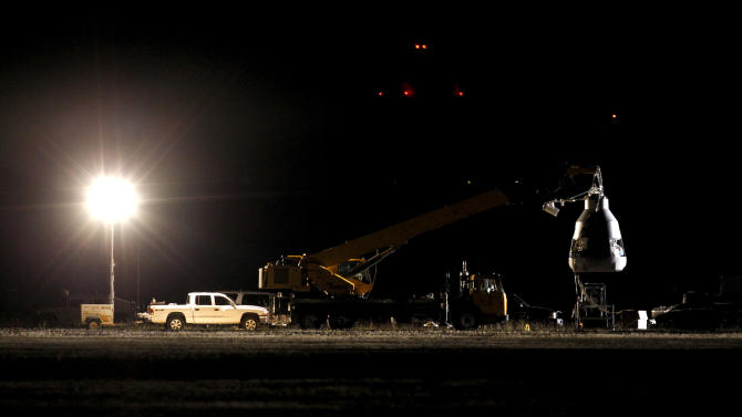 A spotlight illuminates the capsule, ahead of an attempt by Felix Baumgartner to break the speed of sound with his own body by jumping from a space capsule lifted by a helium balloon, Sunday, Oct. 14, 2012, in Roswell, N.M.  Baumgartner plans to jump from an altitude of 120,000 feet, an altitude chosen to enable him to achieve Mach 1 in free fall, which would deliver scientific data to the aerospace community about human survival from high altitudes.(AP Photo/Ross D. Franklin)