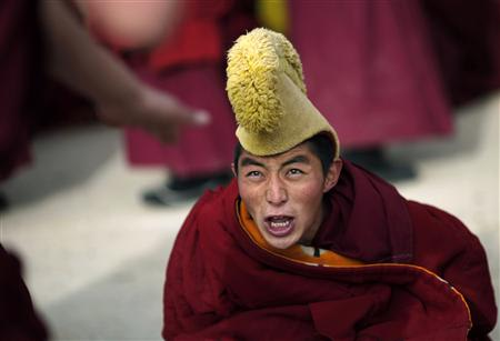 A monk reacts as he participates in a debate as part of Tibetan New Year celebrations at a temple in Langmusixiang, Sichuan Province February 22, 2012. As the number of self-immolations in restive Tibetan regions rises sharply, Beijing appears to be tightening rules against the anti-China protests despite hopes the new leadership may take a softer line against Tibet. Picture taken February 22, 2012. REUTERS/Carlos Barria