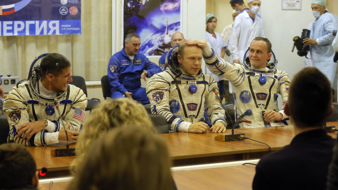 U.S. astronaut Michael Hopkins, Russian cosmonauts Oleg Kotov and Sergey Ryazanskiy, crew members of the mission to the International Space Station, ISS, speak with their familys prior the launch of Soyuz-FG rocket at the Russian leased Baikonur cosmodrome, Kazakhstan, Thursday, Sept. 26, 2013. (AP Photo/Dmitry Lovetsky, Pool)
