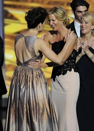 """Betsy Brandt, left, and Anna Gunn of """"Breaking Bad"""" embrace on stage as they accept the award for outstanding drama series at the 65th Primetime Emmy Awards at Nokia Theatre on Sunday Sept. 22, 2013, in Los Angeles. (Photo by Chris Pizzello/Invision/AP)"""