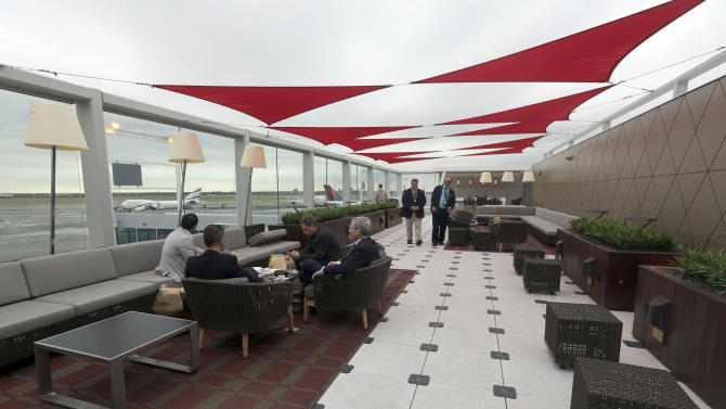 Passengers wait for their flight in the outdoor patio in the Delta airlines Sky club at terminal 4 at JFK airport, Friday, May 24, 2013 in New York. Delta opened its new $1.4 billion terminal, strengthening its hand in the battle for the lucrative New York travel market. The expanded concourse offers sweeping views of the airport, upscale food and shopping options and increased seating. It replaces a decrepit terminal built by Pan Am in 1960 that was an embarrassing way to welcome millions of visitors to the United States. (AP Photo/Mary Altaffer)