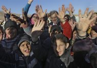 Syrian refugee children cheer as they welcome United Nations High Commissioner for Refugees (UNHCR) Antonio Guterres, center background, during his visit to their refugee camp in the eastern Lebanese border town of Arsal, Lebanon, Friday, Nov. 29, 2013. THE CANADIAN PRESS/AP, Hussein Malla
