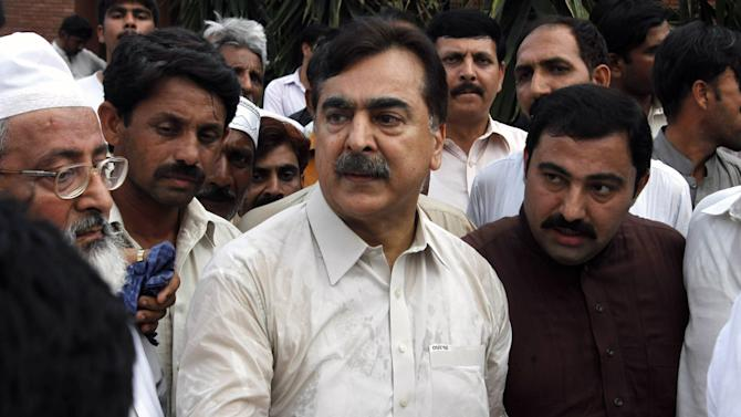 People visit Pakistan's former Prime Minister Yousuf Raza Gilani, center, at his residence in Multan, Pakistan, Thursday, May 9, 2013. Gunmen attacked an election rally in Pakistan's southern Punjab province on Thursday and abducted Ali Haider Gilani,  son of a former prime minister, intensifying what has already been a violent run-up to Saturday's nationwide elections. (AP Photo/Zeeshan Hussain)