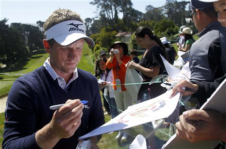 Britain's Luke Donald signs autographs after playing the 18th hole during a practice round for the 2012 U.S. Open golf tournament on the Lake Course at the Olympic Club in San Francisco
