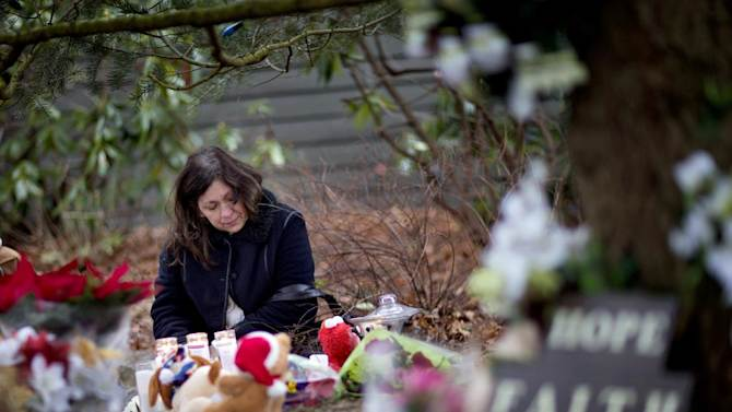 Dilma Steiner, of Newtown, Conn., visits a sidewalk memorial for the Sandy Hook Elementary School shooting victims, Sunday, Dec. 16, 2012, in Newtown, Conn. A gunman walked into Sandy Hook Elementary School in Newtown Friday and opened fire, killing 26 people, including 20 children. (AP Photo/David Goldman)