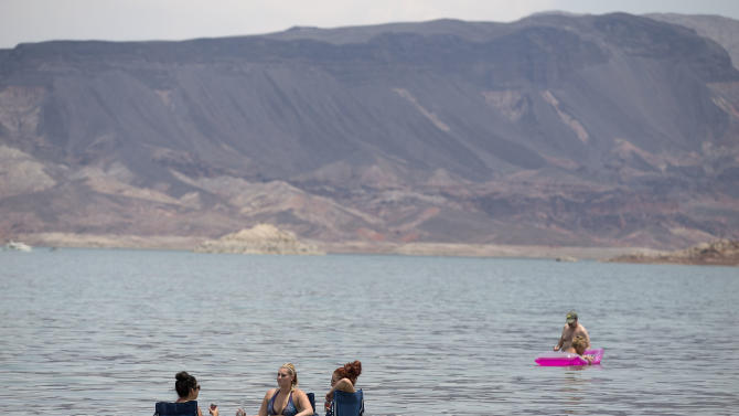 From left, Subrina Madrid, Jennifer, Shackelford and Sarah Hudak, , all of North Las Vegas, Nev., sit in the shallow waters along Boulder Beach at Lake Mead, Saturday, June 29, 2013 near Boulder City, Nev. The three planned to spend the day at the lake to escape the heat in Las Vegas where Saturday's daytime high was expected to reach 117 degrees, which is the city's all-time high. It was 108 at noon Saturday in Sin City. (AP Photo/Julie Jacobson)