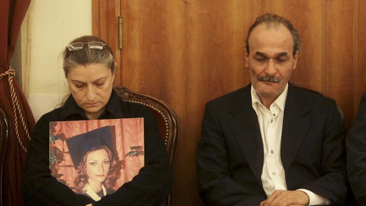 The parents of Cristelle Abou Chakra, with a picture of their daughter, attend her funeral in Beirut