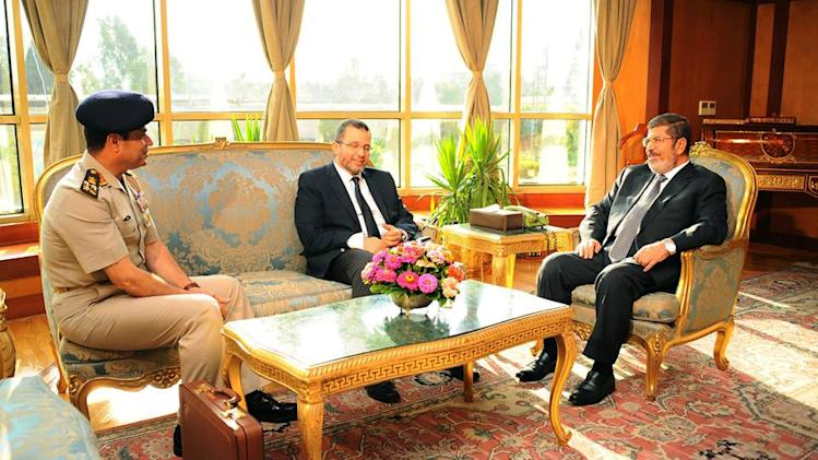 "FILE - In this file photo released by the Egyptian Presidency Monday, July 1, 2013, Egyptian President Mohammed Morsi, right, meets with Prime Minister Hesham Kandil, center, and Egyptian Minister of Defense, Lt. Gen. Abdel-Fattah el-Sissi, left in Cairo, Egypt. ""Over my dead body!"" Mohammed Morsi told his army chief who came to him asking the Islamist president to step down on his own and not resist a military ultimatum and the demands of giant crowds out in the streets. Morsi found himself isolated, with trusted aides abandoning him, and in the end, the ring of Presidential Guards protecting him simply stepped away to allow the military to take him under its custody, according to army, security and Brotherhood officials giving The Associated Press an account of his last hours.(AP Photo/Egyptian Presidency, File)"