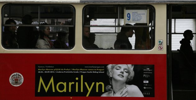 Passengers travel in a tram with an advertisement for a planned exhibition on Marilyn Monroe in central Prague