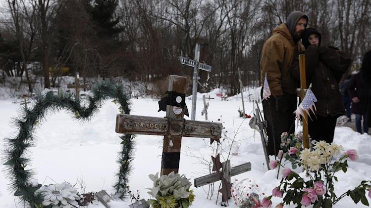 Jason Zubee, left, and his wife Robin Zubee, right, both of North Kingstown, R.I., stand together Sunday, Feb. 17, 2013, in West Warwick, R.I., near makeshift memorials on the site of The Station nightclub fire. Zubee lost her cousin William Christopher Bonardi III in the 2003 blaze at the nightclub that killed 100 people. The Station Fire Memorial Foundation unveiled final plans to build a permanent memorial at the site during ceremonies Sunday. (AP Photo/Steven Senne)