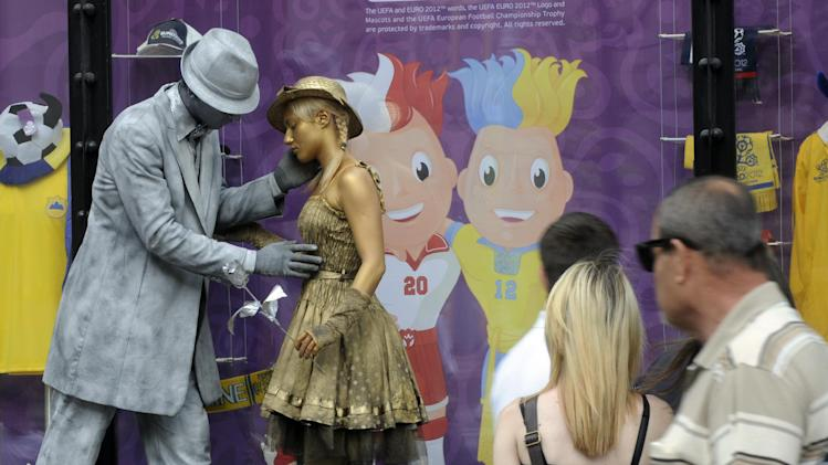 A street actors entertain the passers-by near a storefront with a picture of the Euro 2012 soccer tournament mascots Slavek and Slavko, in central Kiev, Wednesday, May 23, 2012.(AP Photo/Sergei Chuzavkov)