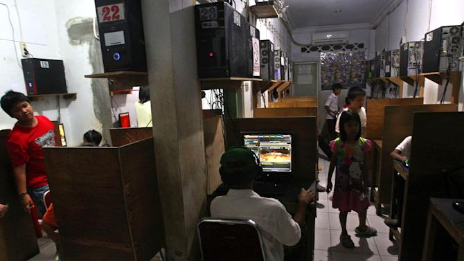 In this June 19, 2013 photo, Indonesian children surf the net at and play games an internet cafe in Jakarta, Indonesia. The use of social networking to groom potential attackers is posing a new challenge to authorities in the world's most populous Muslim country that has been struggling to eradicate militant groups. (AP Photo/Tatan Syuflana)