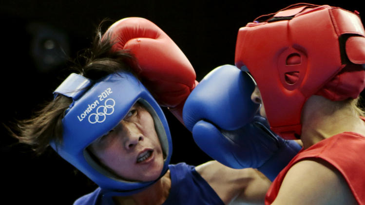 North Korea's Kim Hye Song, left, and Russia's Elena Savelyeva, fight during the women's flyweight boxing competition at the 2012 Summer Olympics, Sunday, Aug. 5, 2012, in London. (AP Photo/Ivan Sekretarev)