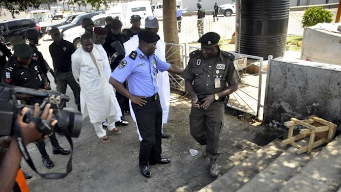 An explosive ordnance device police officer and the Kano State police commissioner inspect the scene of Monday night's bombing by a female suicide bomber at Aliyu bin abi talib mosque in Kano