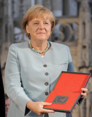 German Chancellor Angela Merkel holds the Emperor Otto Prize in the Cathedral of Magdeburg in Magdeburg, Germany, Wednesday, Aug. 24, 2011. Merkel was awarded with the Emperor Otto Prize for her contribution to greater European integration and stronger European values. (AP Photo/Jens Meyer)