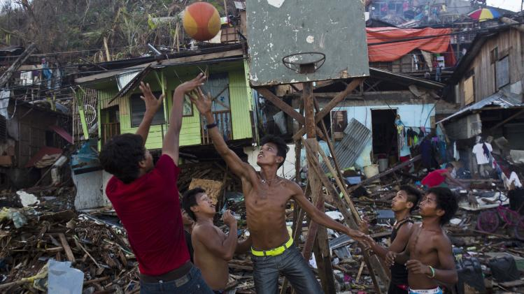 In this Suday Nov. 17, 2013 photo, Typhoon Haiyan survivors play basketball in a destroyed neighborhood in Tacloban, Philippines. They found the hoop in the ruins of their obliterated neighborhood. They propped up the backboard with broken wood beams and rusty nails scavenged from vast mounds of storm-blasted homes. A crowd gathered around. And on one of the few stretches of road here that wasn't overflowing with debris, they played basketball. (AP Photo/David Guttenfelder)