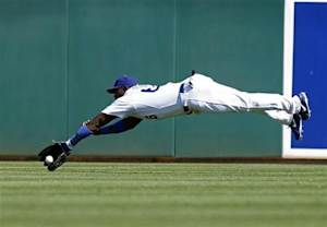 Los Angeles Dodgers Yasiel Puig attempts to make a diving catch of a fly ball off the bat of Cincinnati Reds' Brandon Phillips during their MLB Cactus League spring training baseball game in Glendale