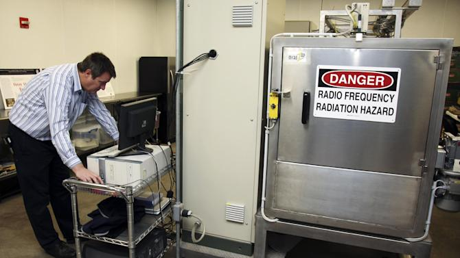 In this Dec. 6, 2012, photo, Andreas Neuber, an electrical engineering professor at Texas Tech University, monitors a high powered microwave at Microzap, Inc., in Lubbock, Texas. Chief executive officer Don Stull says the company's technology allows bread to stay mold-free for 60 days. The bread is bombarded with microwaves for about 10 seconds, which kills the mold spores, he said. (AP Photo/John Mone)