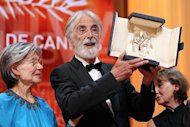 "Austrian director Michael Haneke raises his trophy as he poses with French actress Emmanuelle Riva after being awarded with the Palme d'Or for his film ""Amour"" during the closing ceremony of the 65th Cannes film festival in Cannes"